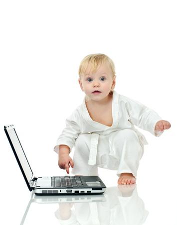 little boy in kimono about laptop on white background Standard-Bild