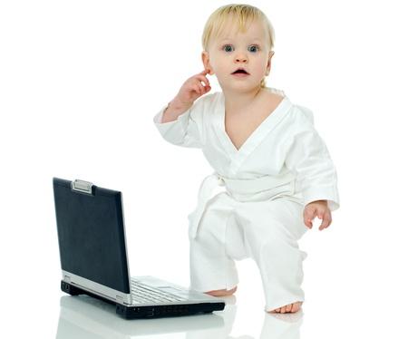 little boy in kimono about laptop on white background photo