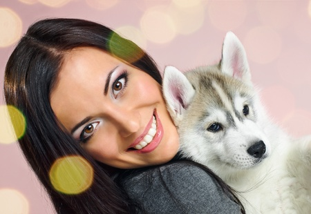 playing woman with puppy of siberian haski on pink background with confetti photo