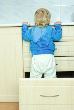 white haired little boy in the kitchen cabinet from the back  photo