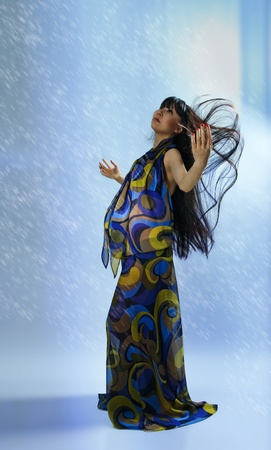 asian pregnant woman in transparent dress on blue background with radiance  photo