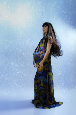 radiance: asian pregnant woman in transparent dress on blue background with radiance  Stock Photo