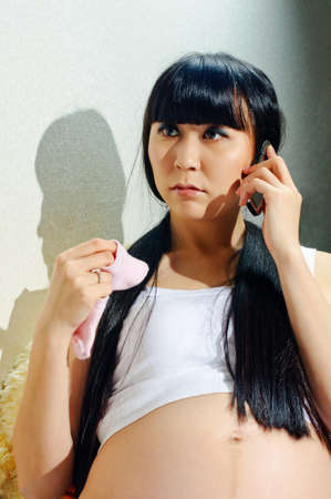 young pregnant woman talks by phone with baby sock photo