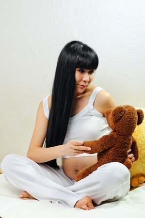 young pregnant woman plays with bear toy photo