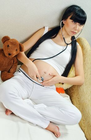 young pregnant woman feels her baby in tummy  Stock Photo - 9081869
