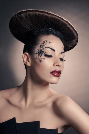 portrait of beautiful girl with coiffure disc on grey Standard-Bild