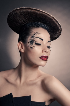 portrait of beautiful girl with coiffure disc on grey photo