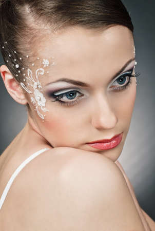 portrait of beautiful girl bride with coiffure and make up on grey Stock Photo - 9666510