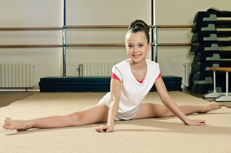 portrait of young beauty gymnast in gymnasium