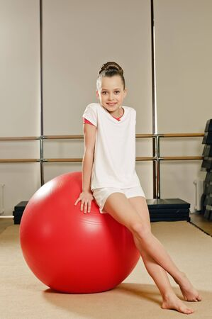 portrait of young beauty gymnast in gymnasium on the ball  photo