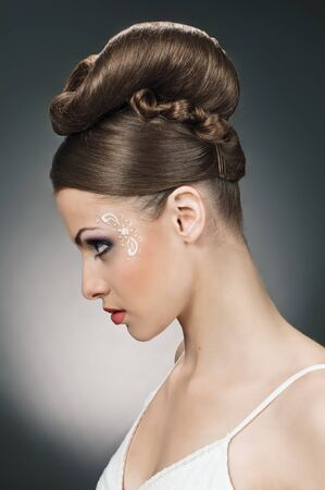wedding hairstyle: portrait of beautiful girl bride with coiffure and make up on grey