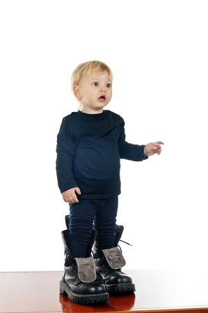 trying: two years old boy in big shoes on white