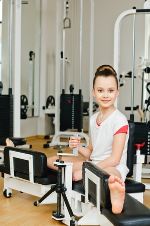 portrait of young beauty gymnast in gymnasium  photo