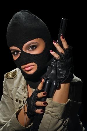 young beauty girl with machine-gun on black background Standard-Bild