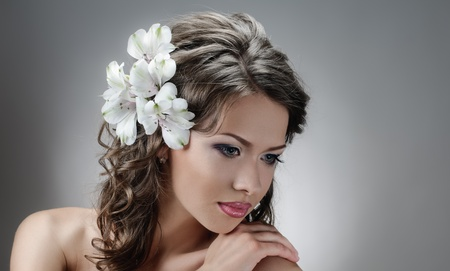 wedding hairstyle: portrait of beautiful bride with flowers in hair on grey