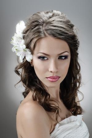 hochzeitsfrisur: Portrait der sch�nen Braut mit Blumen im Haar auf grauem