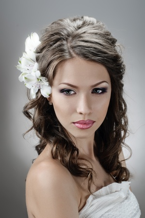 portrait of beautiful bride with flowers in hair on grey photo