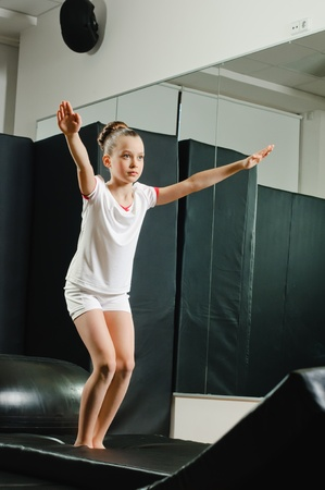 skids: young beauty gymnast in gymnasium before jump