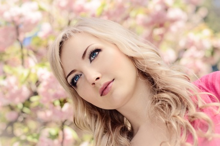 portrait of beautiful girl with blooming sakura on background photo