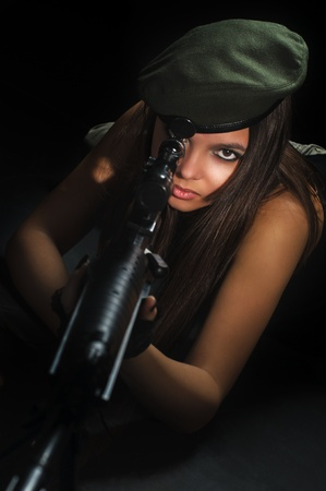 young beauty girl with machine-gun on black background photo