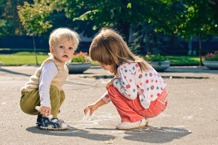 little boy and girl with crayons, they drawing on the asphalt photo