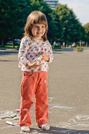 little girl with crayons in the park photo