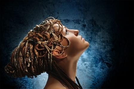 artificial hair: retrato de la hermosa chica con trenzas africanas sobre fondo gris
