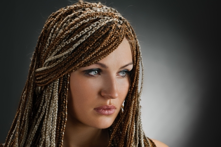 artificial hair: portrait of beautiful girl with african plaits on grey Stock Photo