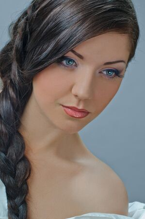 portrait of beautiful girl with plait ongrey photo