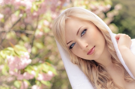 portrait of beautiful girl with white kerchief and blooming sakura on background photo