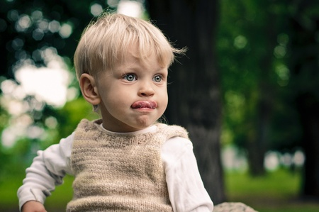 reverie: little boy shows his tongue in reverie