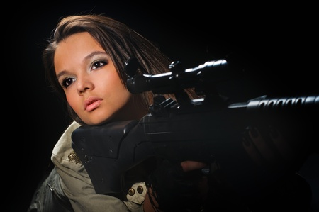 commando: young beauty girl with machine-gun on black background Stock Photo