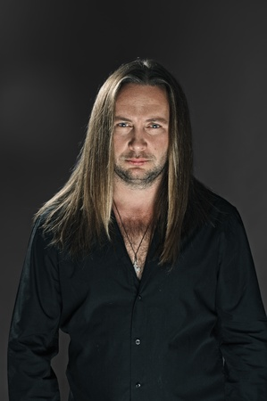 portrait of man with long hair on grey Stock Photo