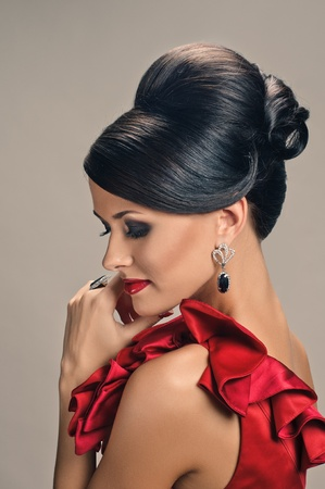 grey hair female: portrait of beautiful girl with elegant coiffure and red dress on grey