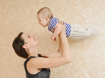 young mother and her baby in the room about wall with wall-paper photo