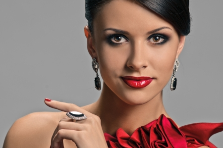 portrait of beautiful girl with elegant coiffure and red dress on grey photo