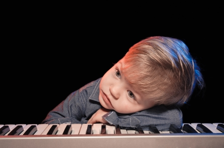 little boy with the keyboard on black background     photo