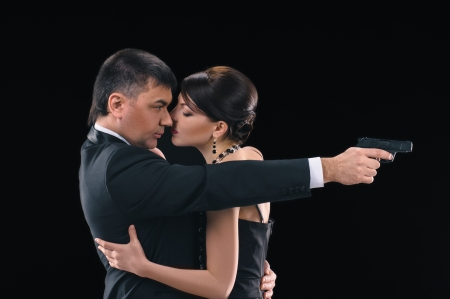 embracing woman and man on black background, man holds a pistol photo
