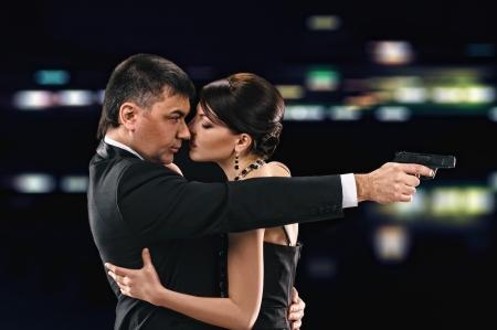 dangerous love: abbracciando donna e uomo su sfondo notte, l'uomo detiene una pistola