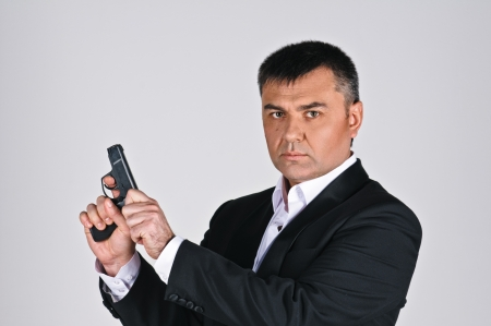 man in suit with pistol on grey background photo
