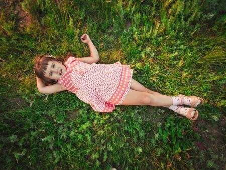 little girl on grass on the field photo