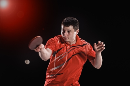 young man tennis-player in play on black background with lights