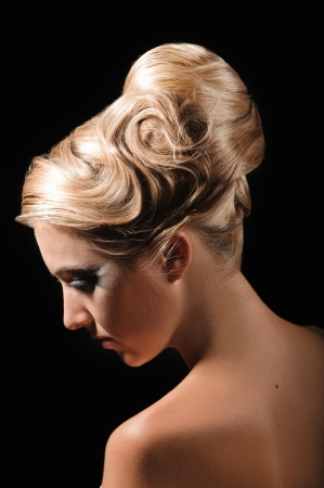 half face portrait of beautiful peroxide blonde girl with coiffure on black background photo