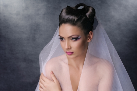 portrait of bride with coiffure and make up on grey photo