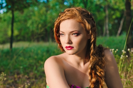 red haired young woman with plait in summer photo