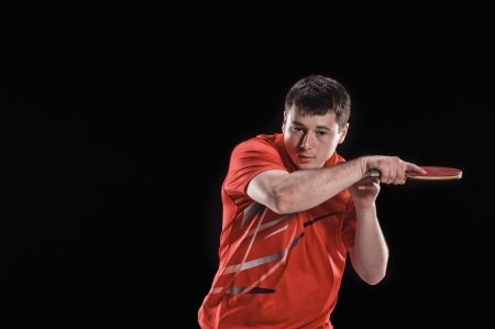 young man tennis-player in play on black background Banque d'images