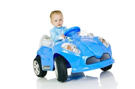 little boy in blue electro car on white