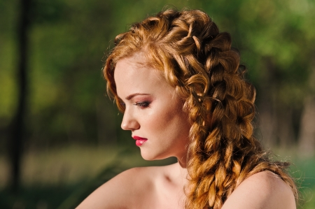 girl in the forest: red haired young woman with plait in summer