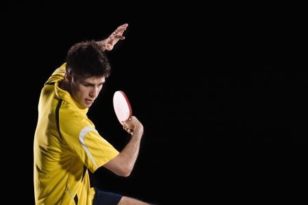 tennis de table: jeune homme joueur de tennis en jeu sur fond noir avec des lumi�res