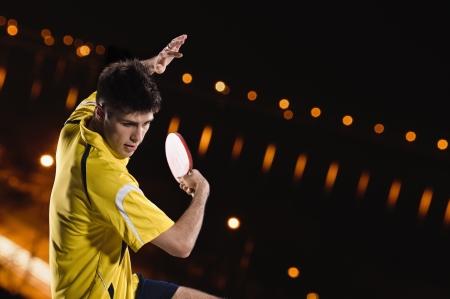 tischtennis: junger Mann Tennisspieler im Spiel auf schwarzem Hintergrund mit Lichtern Lizenzfreie Bilder